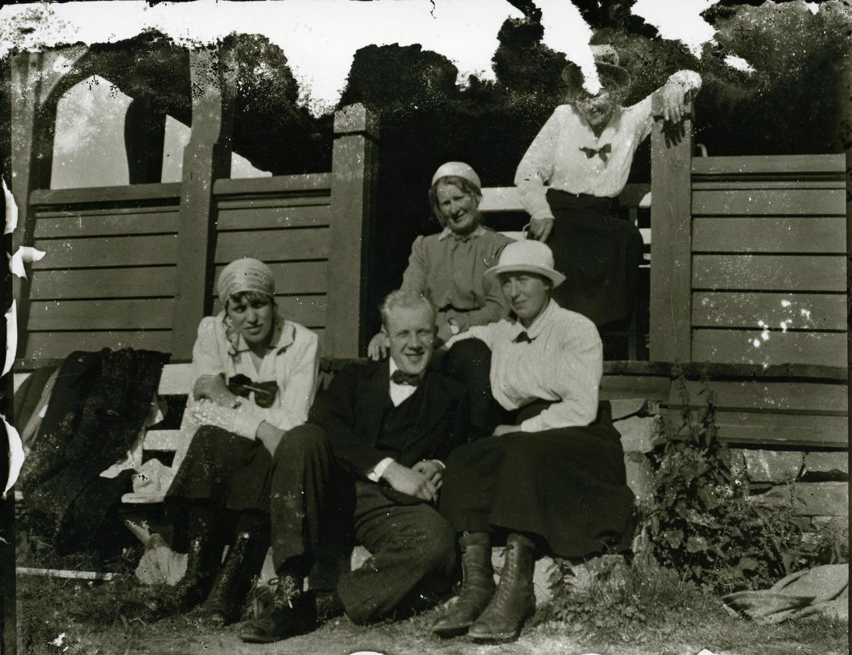 Fire kvinner og en mann sitter på ei trapp. Sannsynligvis Gausdal Høyfjellshotell.