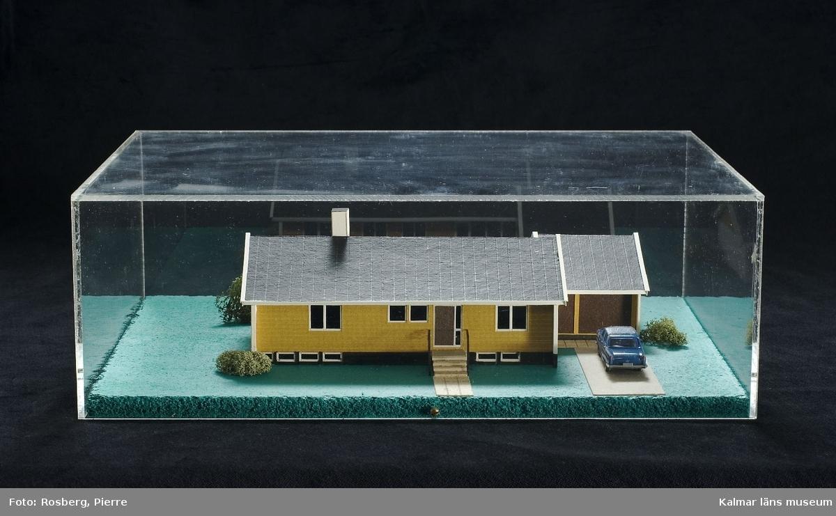 KLM 28685:2 Husmodell av trä mm. Modell i skala 1:100 av ett monteringsfärdigt småhus från Hultsfredshus med beteckningen A104-B10. Naturliga färger. Monterat på tunn grönmålad spånplatta och täckt med en huv av plexiglas.