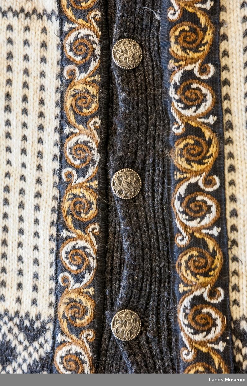 Strikket jakke med lange ermer i to farger. Pyntebånd langs hals og stolpe, brun og kvit. 7 metallknapper. Mønster: Ol-genseren fra Lake Placid 1980. Design: Dale of Norway