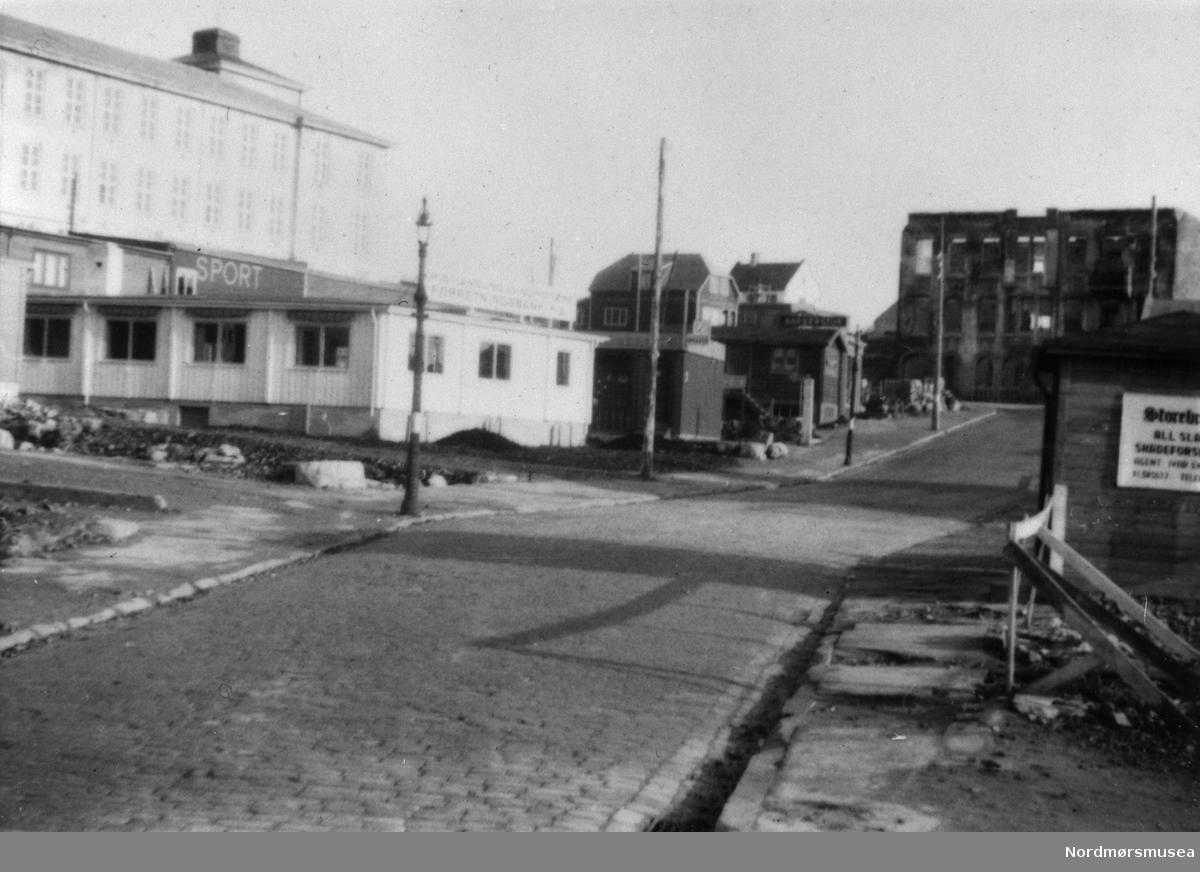 Nedre Enggate i Kristiansund 1940. Sportsforretning, Forretningsbanken og Storebrand forsikring i brakker. Gymnaset/KOHAS (seinere Langveien Ungdommsskole) til venstre  Nordmøre museums fotosamling