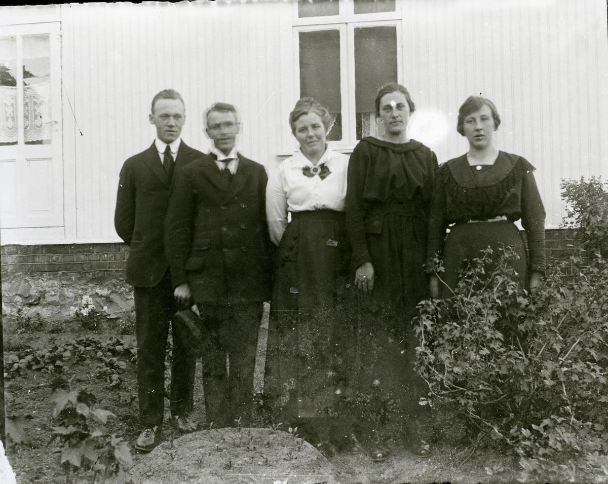 Ei gruppe er avbilda i hagen utanfor eit kvitt hus.