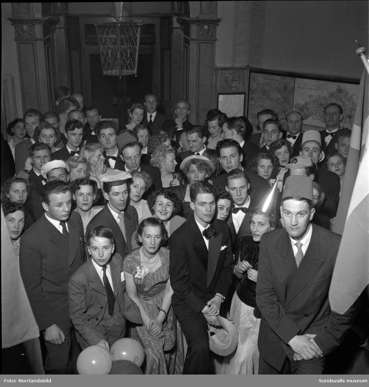 Nyårsfirande på Knaust med bland annat klockringning i den berömda trappan och en ung dragspelare som får förtroendet att förvalta nyckeln till det nya året 1951. (Eventuellt Lars-Erik Sundbom.)