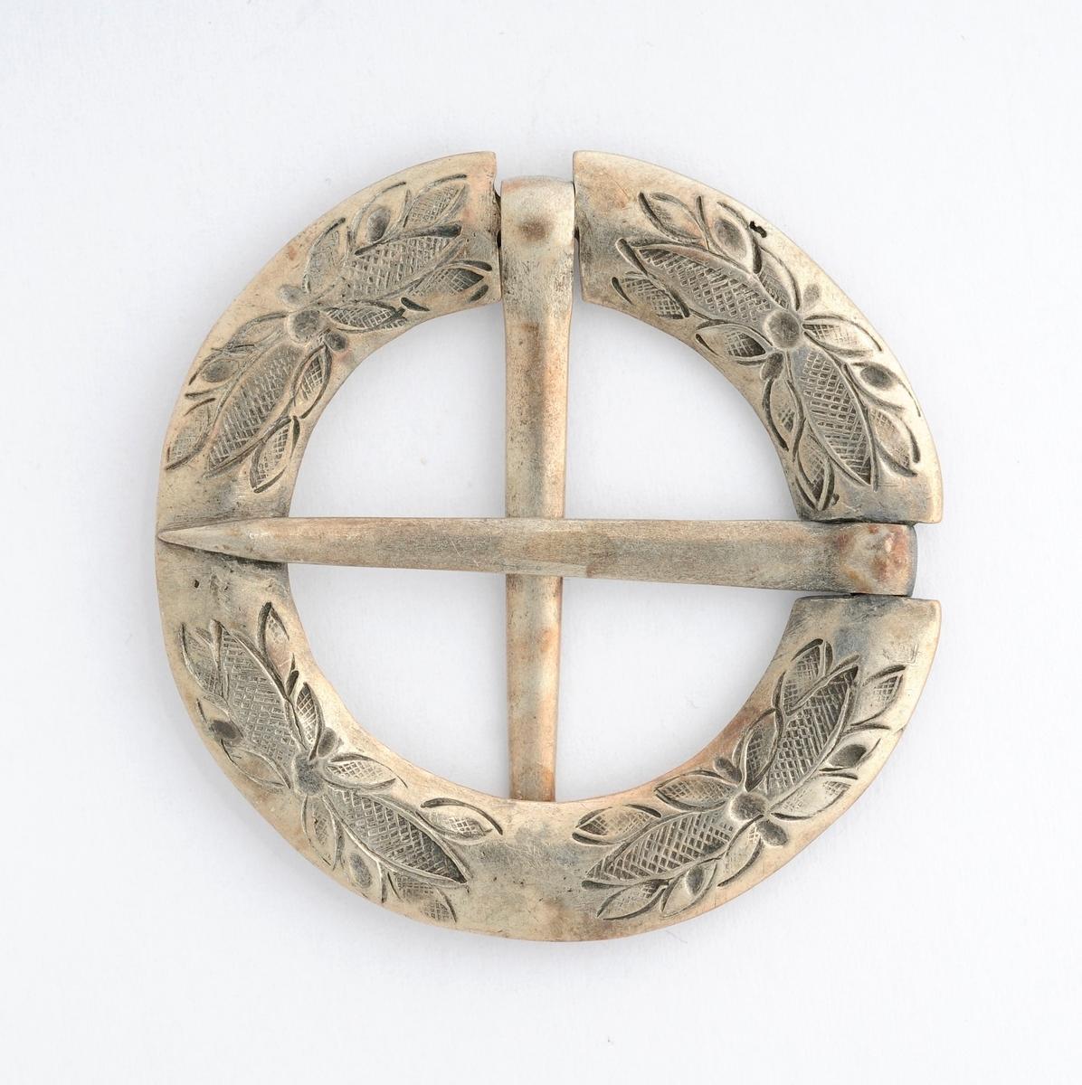 Sølje, krossnål i sølv (utan stempel). Rund, (støypt ?) med to nåler i kors. Den eine nåla er fastlodda. Gravert rosemønster på framsida. Glatt på baksida.