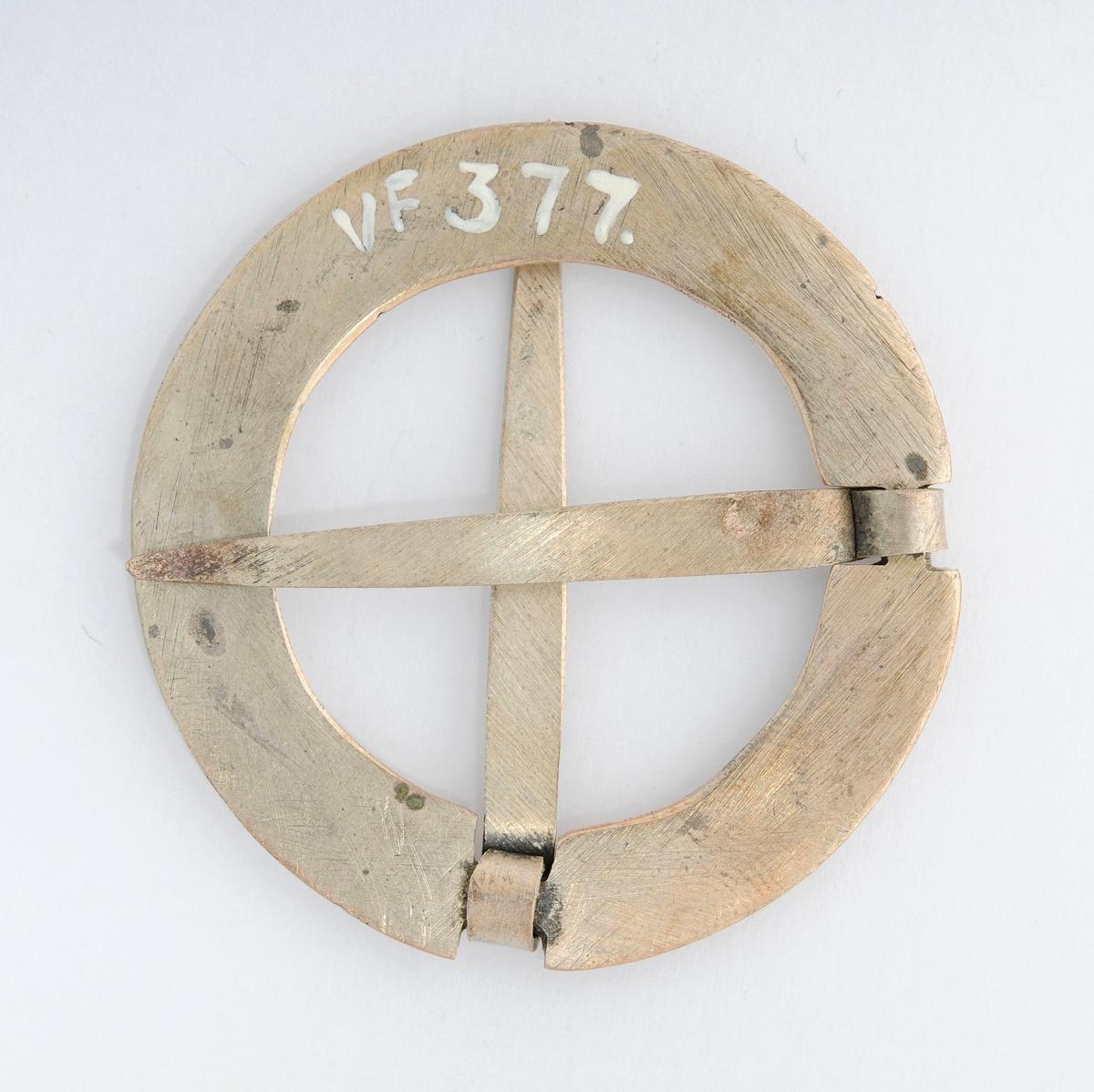 Sølje, krossnål i sølv (utan stempel). Rund, (støypt ?) med to nåler i kors. Gravert rosemønster på framsida. Glatt på baksida.
