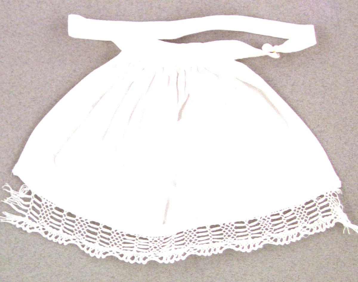 Dockförkläde av vitt bomullstyg med påsydd knypplad spets i nederkanten. Ett linningsband runt midjan som fästes med en tryckknapp