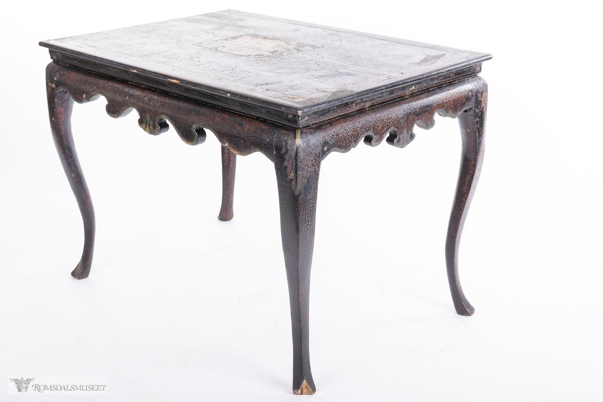 Et stilleben sentralt på bordplaten av en klase med plommer, to fersken, den ene brutt åpen, to nøtter og en fiken.