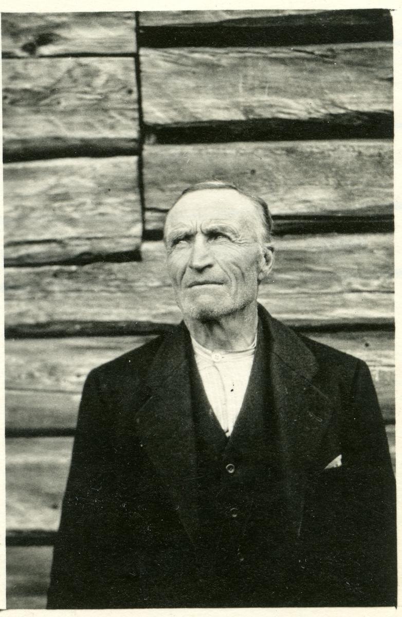 Ein eldre mann sit foran ein husvegg.