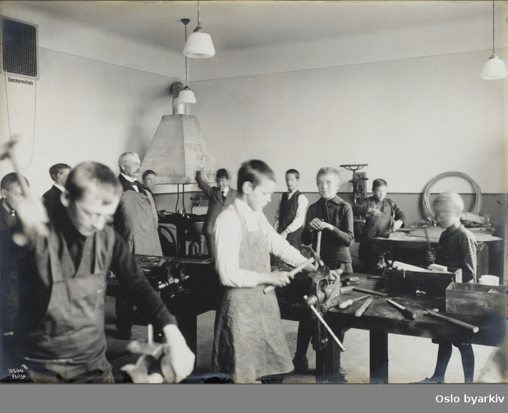Sløydsal, gutter ved arbeidsbenk, lærer. Esse (?) i bakgrunnen, metallarbeider, smedarbeid (?) Ila skole 1916 (albumtittel)