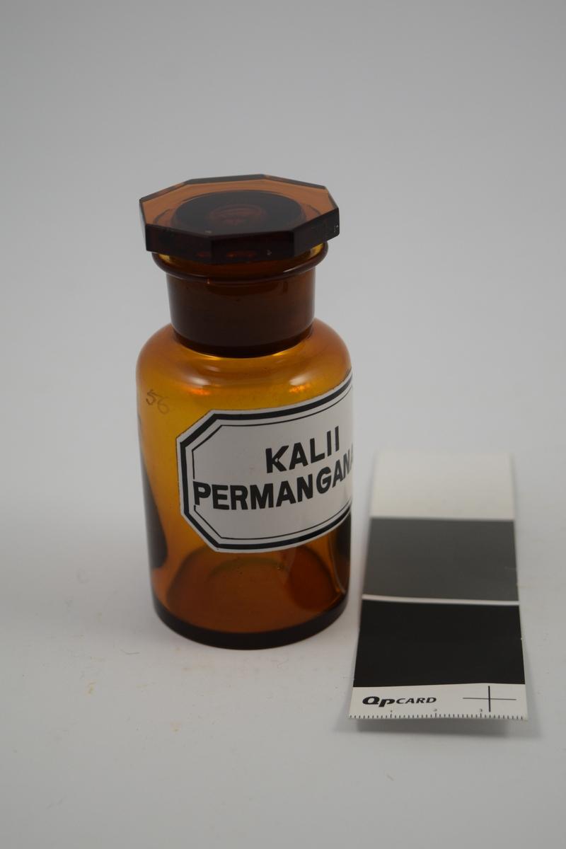 Brun glasskrukke med glasspropp. Hvit etikett med sort skrift. Kalii permanganas ble brukt i badevannet ved eksem, barneeksem. Oppløses i vann.