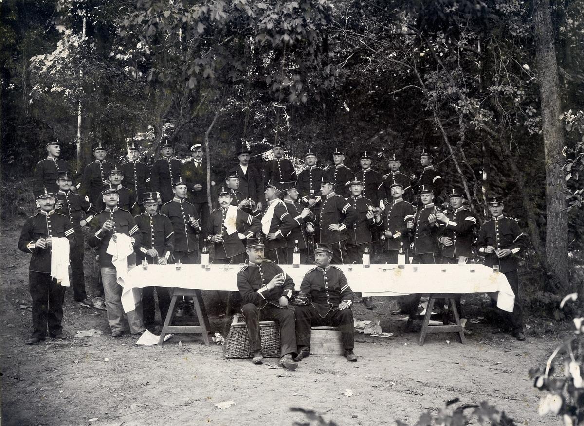 Soldater vid dukat bord med vinflaskor och glas.