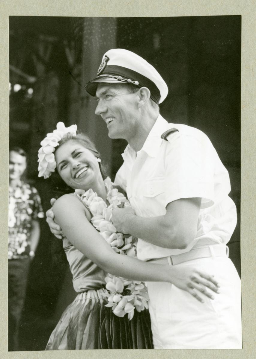 Bilden föreställer en besättningsmedlem i vit uniform som omfamnar en kvinna utsmyckad med blommor i håret och runt halsen. Bilden är tagen i samband med minfartyget Älvsnabbens långresa 1966-1967.
