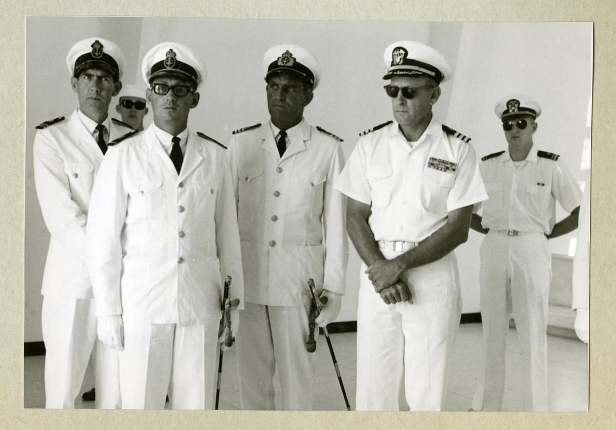 Bilden föreställer en grupp officerare i vita uniformer vid minnesmonumentet över attacken mot Pearl Habour på Hawaii. Längst till vänster i bilden står Oskar Linde. Fotot är taget under minfartyget Älvsnabbens långresa 1966-1967.