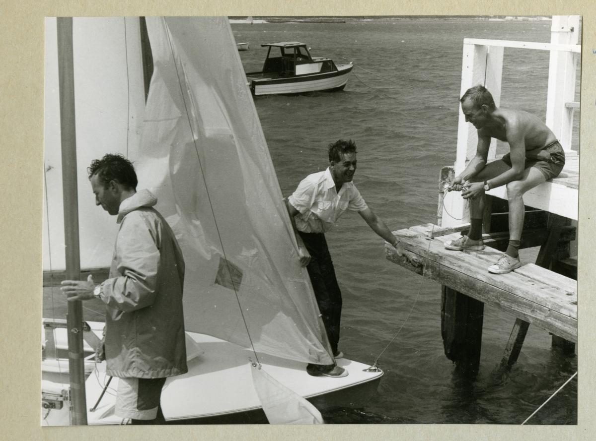 Bilden föreställer tre män. En sitter på en brygga, en står på en liten segelbåt och en håller i en mast. I bakgrunden syns en liten motorbåt. Bilden är tagen under minfartyget Älvsnabbens långresa 1966-1967.