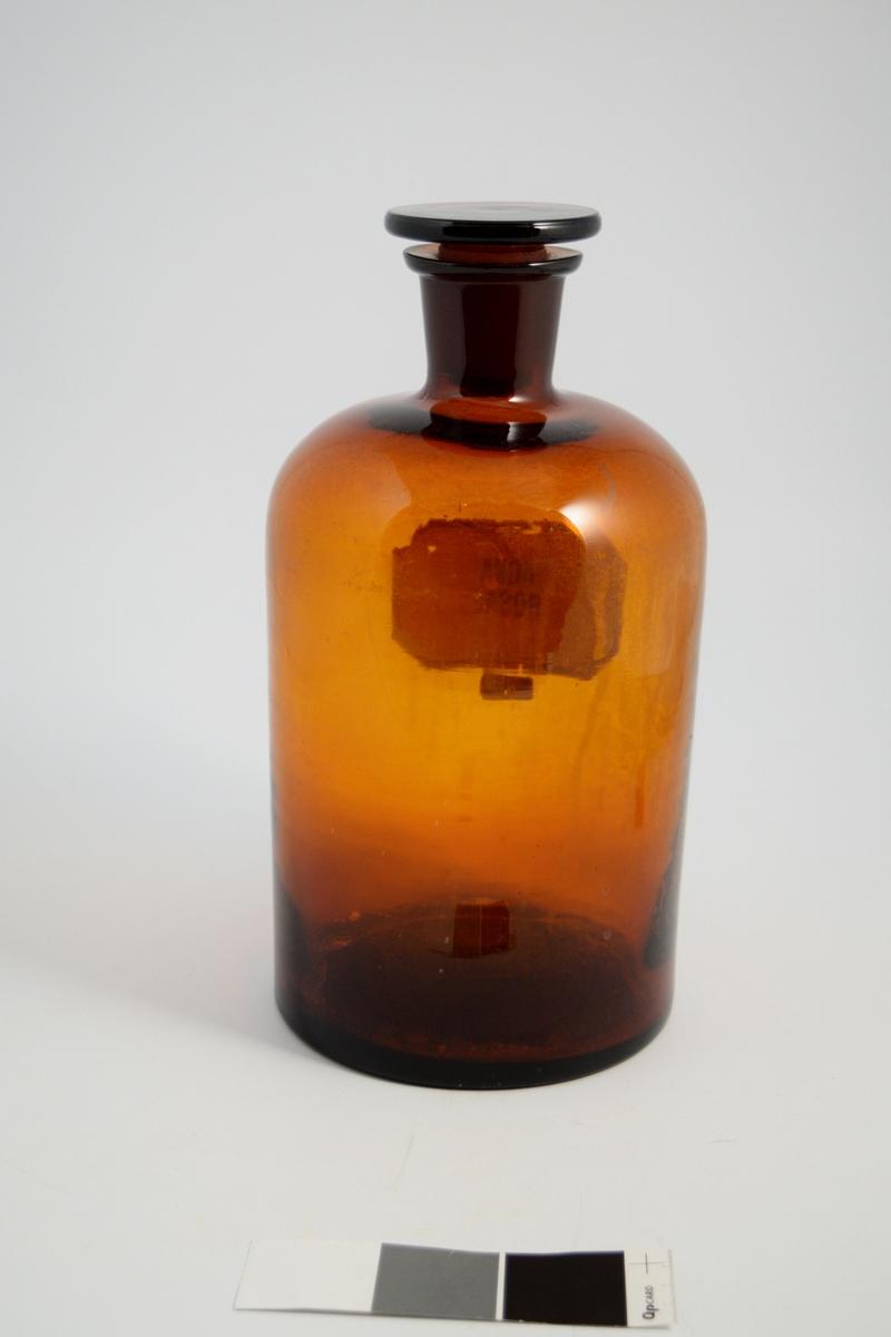Brun glassflaske, smal hals, brun glass propp. Påført hvit etikett med sort skrift. Brukt til oppbevaring av løsninger. Aqua rosae (rosevann) ble brukt til hudpreparater, dufttilsetning.