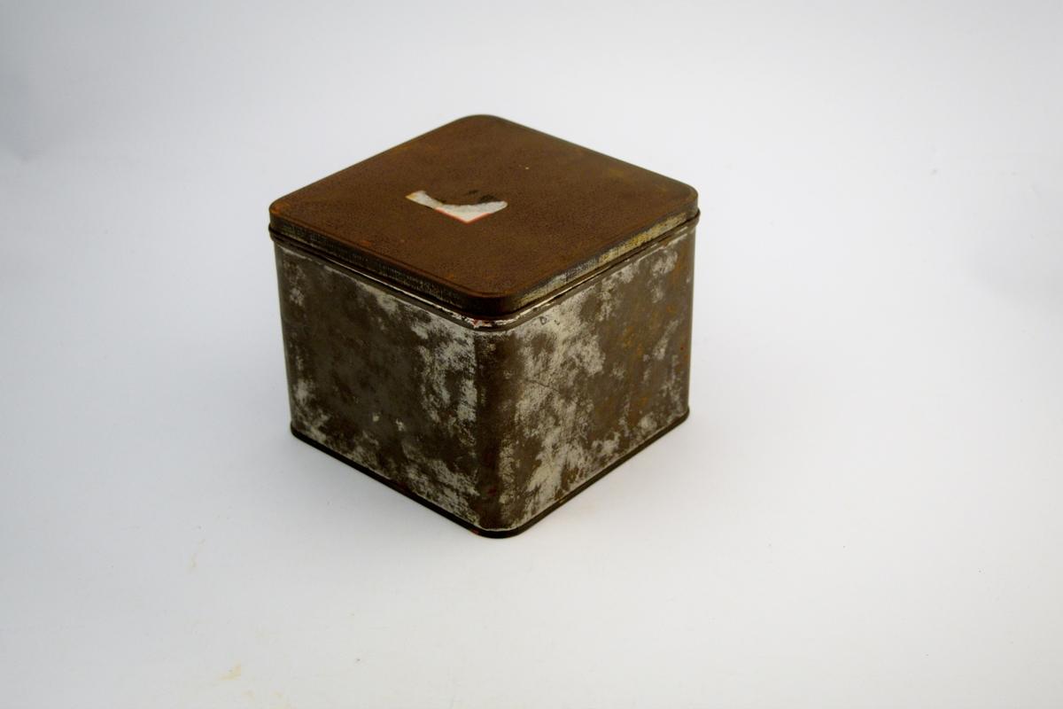 Rektangulær blikkboks med lokk. Råvarer ble kjøpt inn i slike bokser i forskjellige størrelser. Inneholdt diverse tørre varer som ofte ble brukt i produksjon av legemidler. Boksene med innhold ble levert av NMD (Norsk medisinaldepot).