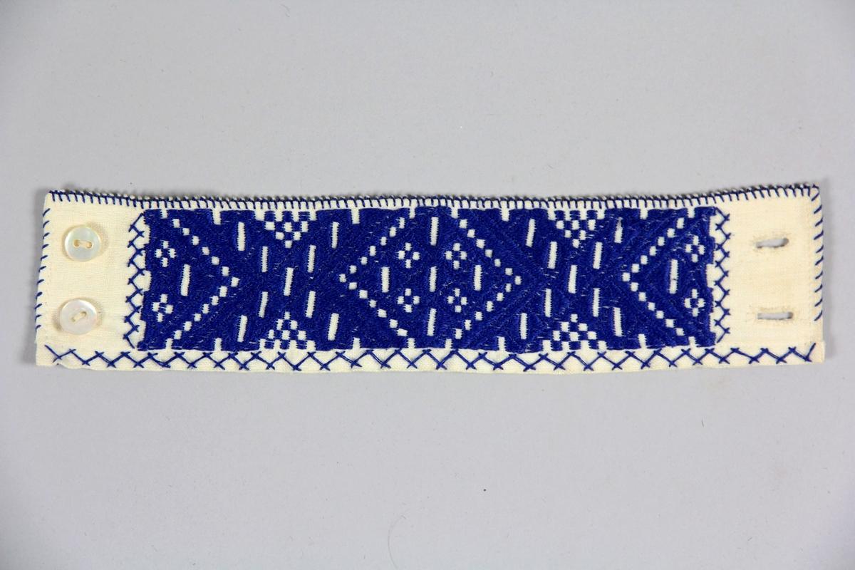 Ett par ärmlinningar till Rättviksdräkten, för kvinna. Broderade med blått platsömsbroderi, nuggor och flätsöm. Knäpps med två pärlemorknappar på vardera liningen.