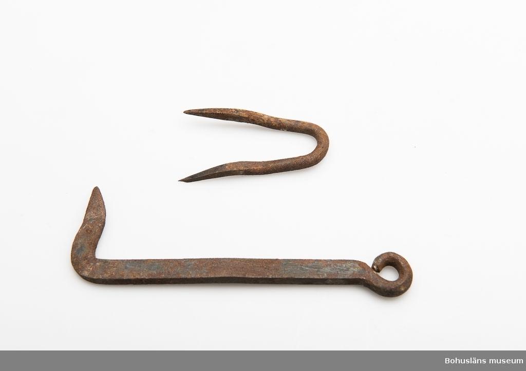 Krok med krampa för dörr. Något rostangripna. 12,7 cm är krokens längd och dess bredd är 4,2 cm.