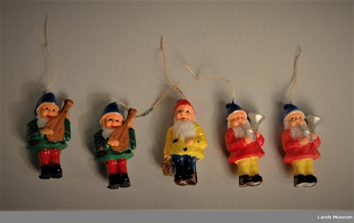 5 stk julenisser i plast med snor for oppheng i tre. 1 nisse med lykt i handa, 2 stykker med eit blåseinstrument og 2 stykker med eit strenginstrument.