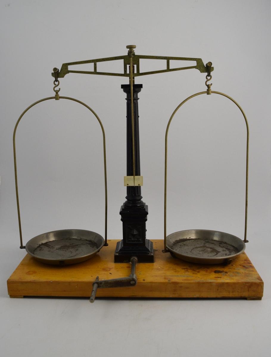 Metallvekt montert på lakkert treplate, stammen sortlakkert, skåler av sink(?). Messingoppheng. Fra 5 g. til 2 kg.