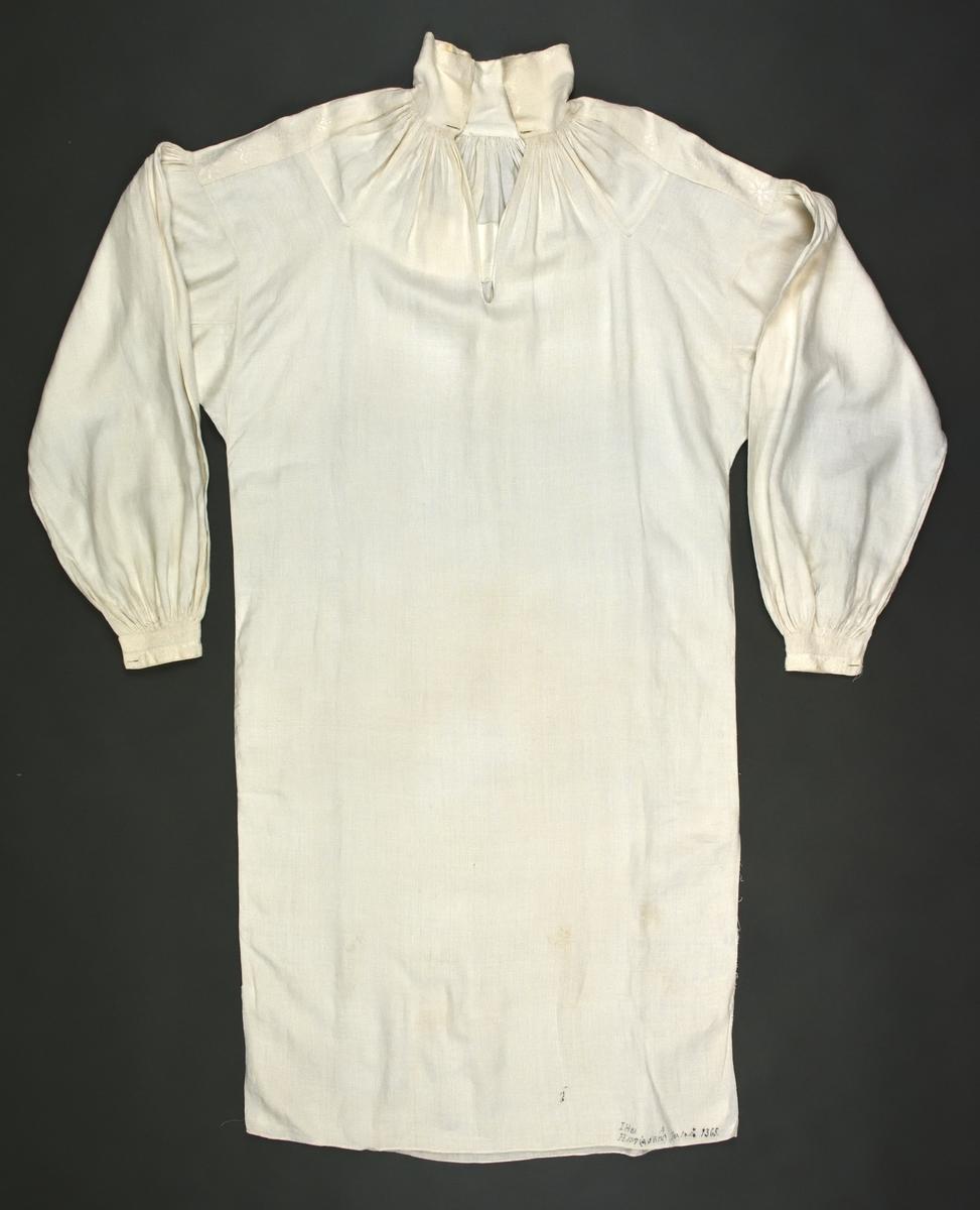 Handvävd och handsydd brudgumsskjorta med hals- och ärmspjäll. Broderad i rätlinjig plattsöm på axelklaffarna, kragen och ärmlinningarna. Stripade rynkor vid halsen och ärmlinningarna, som även har nuggor. Nött i ryggpartiet. Vådbredd 580 mm, ärmlängd 600 mm, kraghöjd 90 mm.