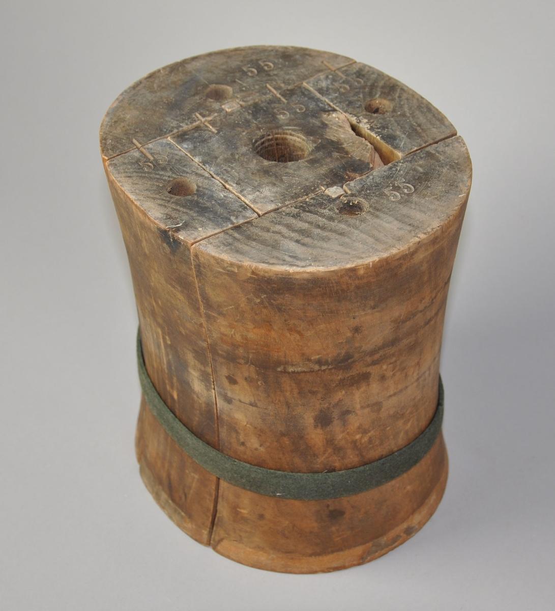 Sylinderformet hatteblokk hvor midtpartiet er innsnevret. Består av fem deler som holdes samlet av en tekstiltråd. På undersiden av formen er det hull for skruefeste på alle tredelene.