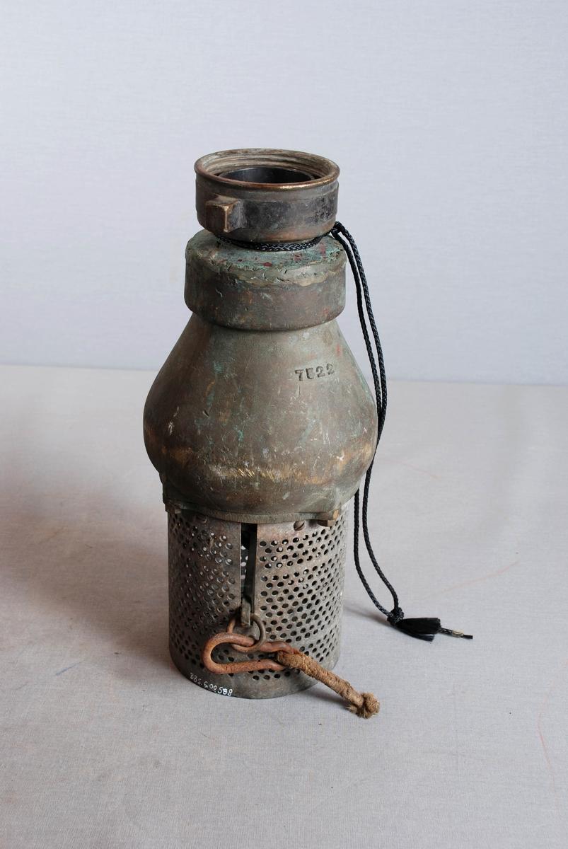 Løkformet sil i metall, til sugeslange for brannvesen. Sylinderformet sokkel av perforert metall med en loddrett spalte for hendel festet inne i sokkelen. I enden av hendelen er det festet karabinkrok. Slangekupling i toppen.