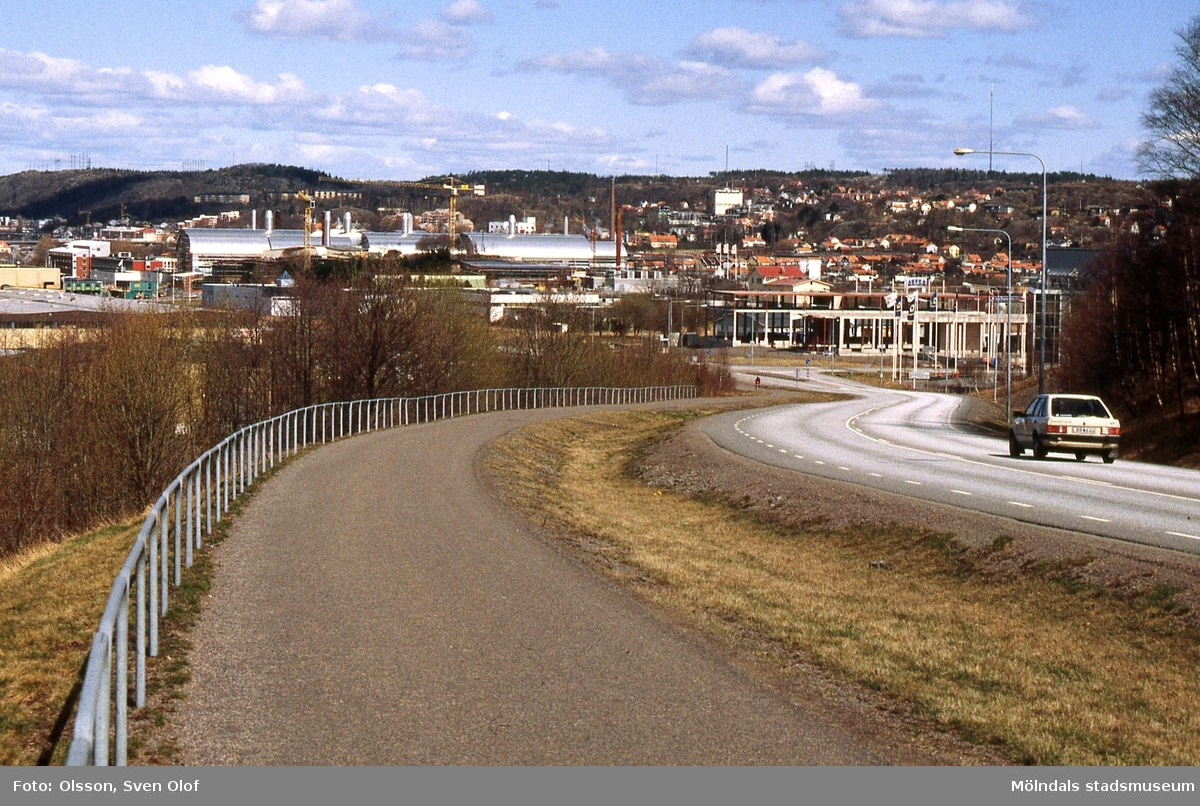 Vy från Pepparedsleden mot bebyggelse i Åbro industriområde, Mölndal, år 1993. Till höger nedanför backen ses Bäckeviks ofullbordade byggnad. Företaget gick i konkurs. Kä 6:9.