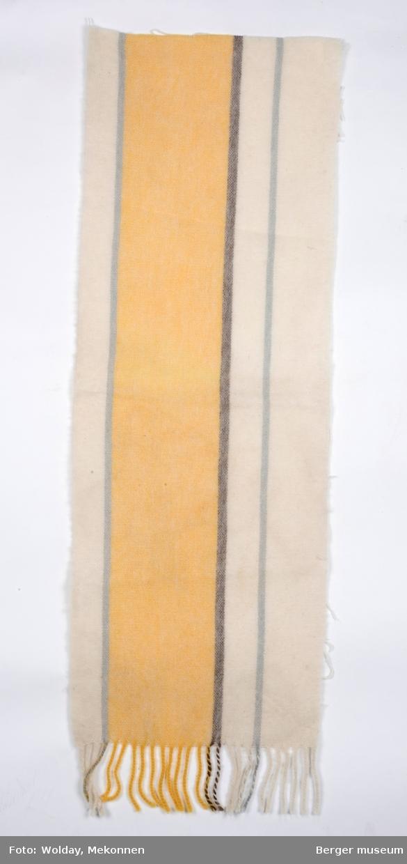 En avlang pleddprøve med stripemønster langs lengderetning; et bredt gult felt er adskilt av grå striper på hver side, og har hhv to og ett stripefelt i offwhite på hver side. Den ene lyse stripefeltet er delt av en smal grå stripe. Prøven har klippede kanter, og frynsekant på ene kortenden.