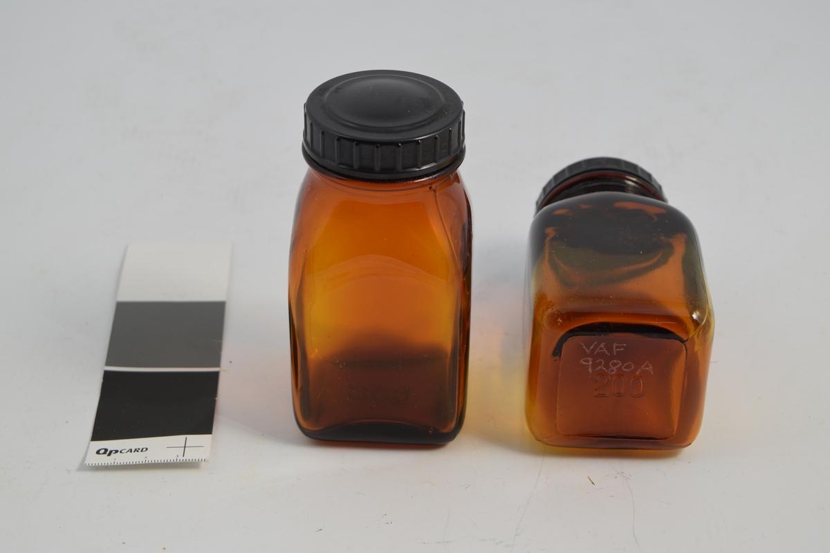 2 stk. brune, transparente, firkantede glasskrukker med sort rundt bakelitt lokk. Brukt til oppbevaring av tabletter i apotek og for salg.