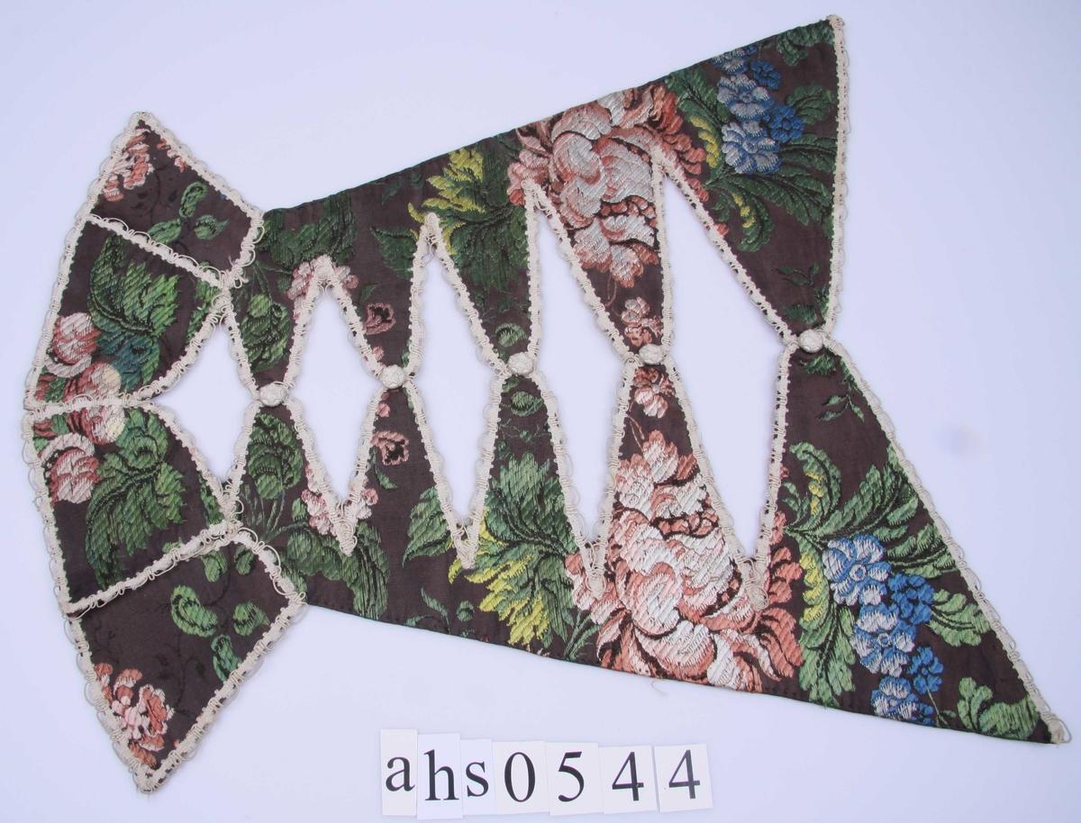 Av sort silke brochert med blomstermønster i rødt, rosa, to blå og to grønne farger. Brystduken er utskåret i spisser mot midten og flikene er kantet med hvit possement-lisse og har en overtrukket knapp med stjerne på midten. Nederst ender brystduken i fire rett avskårne fliker kantet på samme måte. Fôr av rødlig, vokset linlerret.