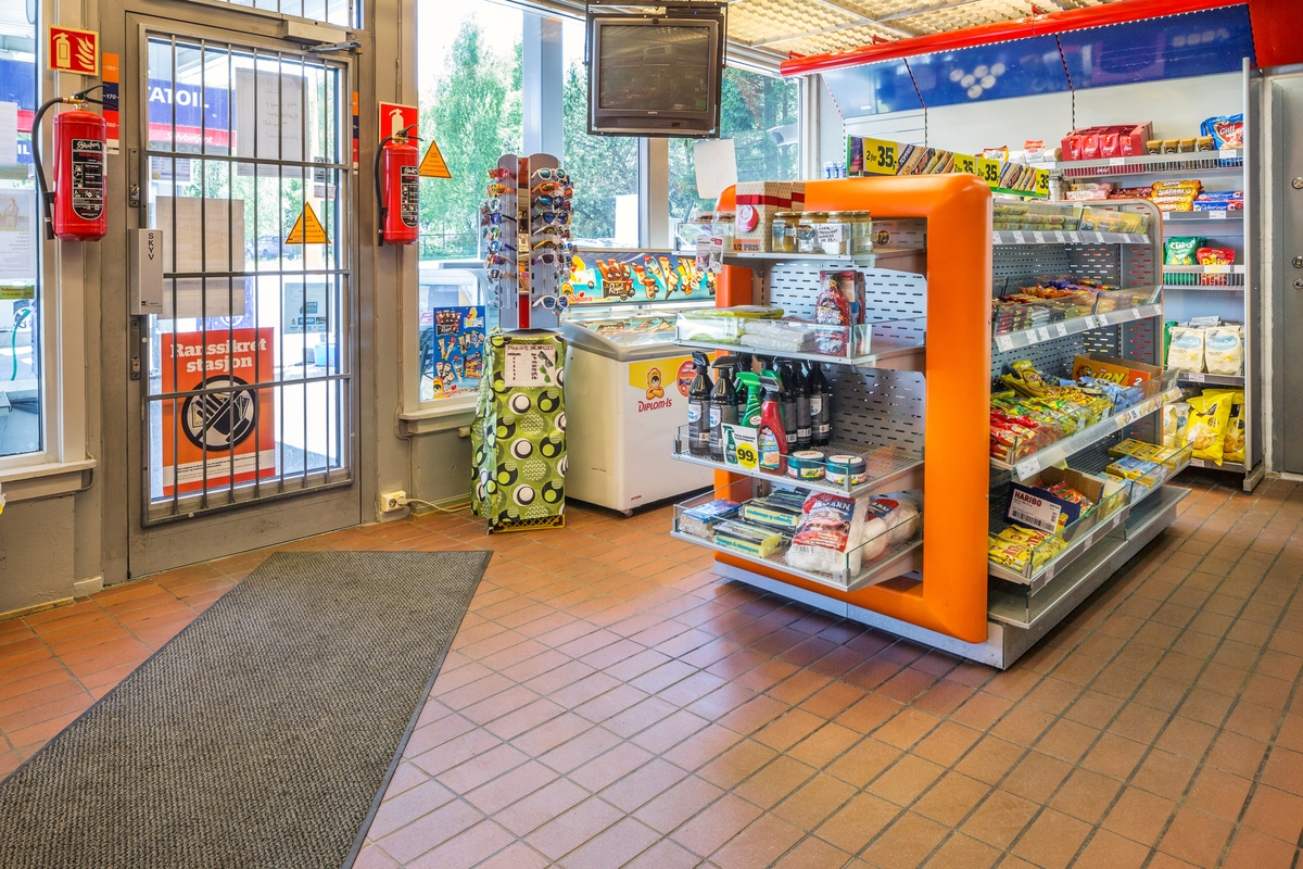 Statoil Hemnes. Butikk interiør med hylleseksjoner med varer. Inngangsdør og stativ med solbriller og en frysebok med iskrem.