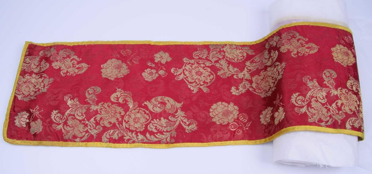 Av rød silkedamask med brocherte blomster i gulltråd, skjøtt sammen av tre stykker. Linnen er kantet med gult silkebånd og fôret med gulrødt vokset lerret.