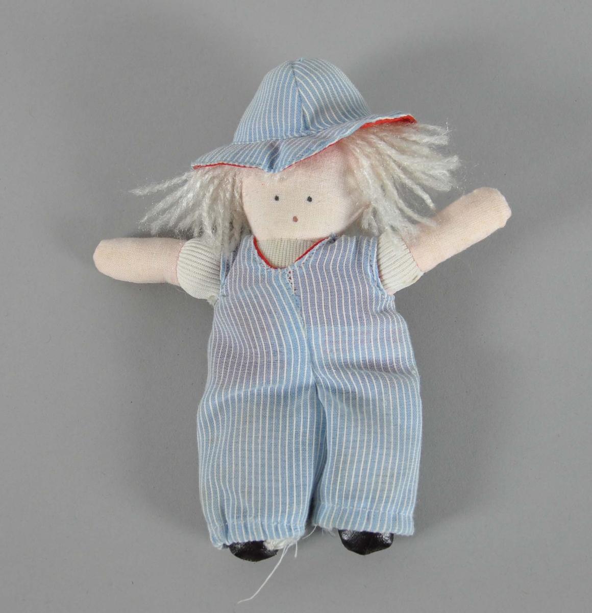Hjemmelaget dukke. Dukken er hvit og har hvitt langt hår. Hatt og overall er blå med hvite striper.