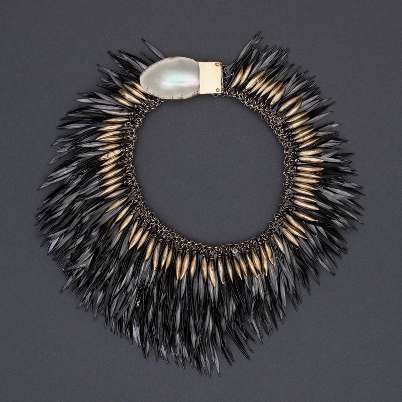 Halssmykke med brynje av sølv, hvorpå det er festet rader av flate, hammrede fjærlignende stålnagler. Også elementer av gull og perlemor langs den indre kanten.