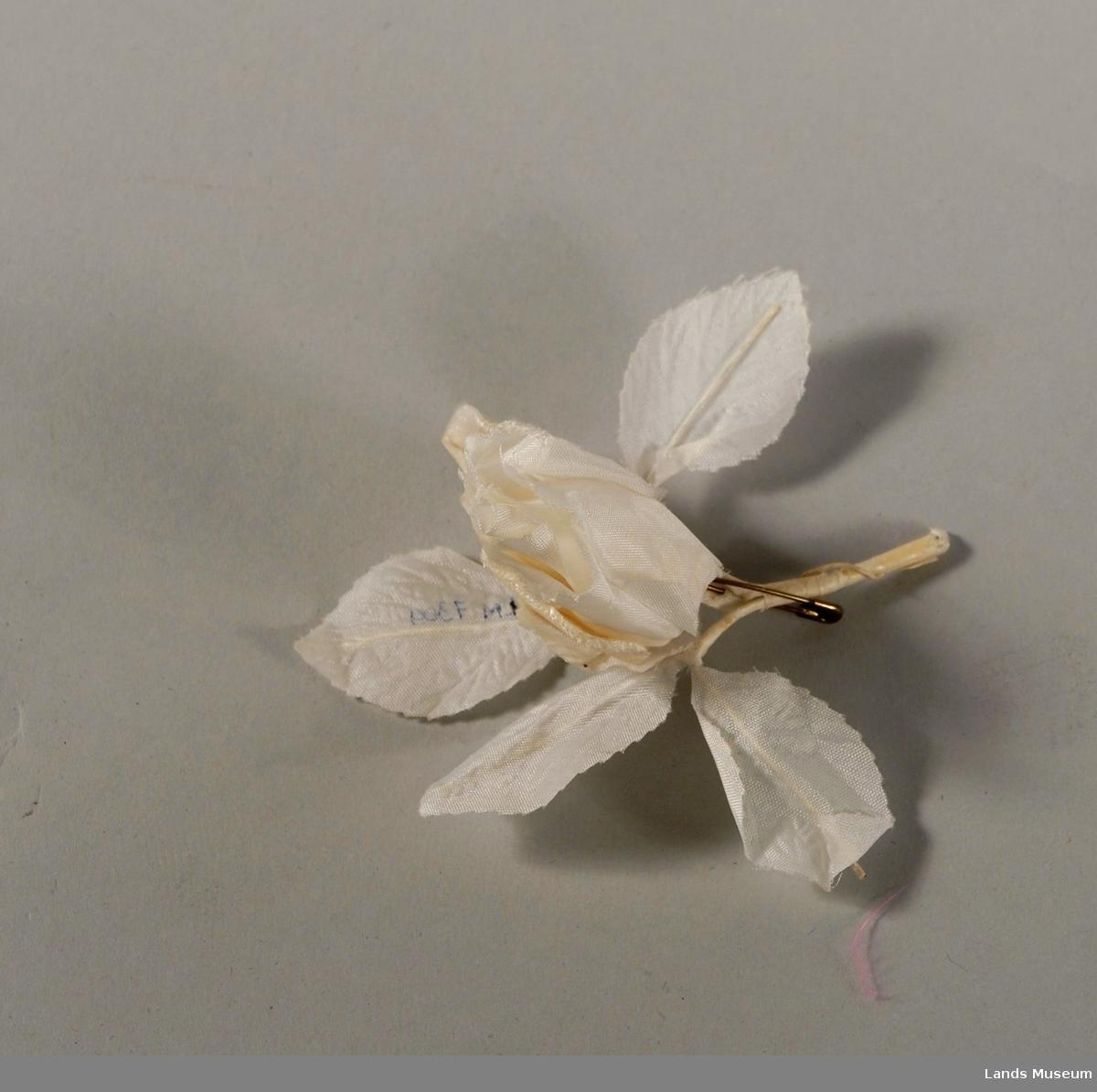 Rose, hvitt silkestoff. Med sikkerhetsnål for feste, messingfarget metall.