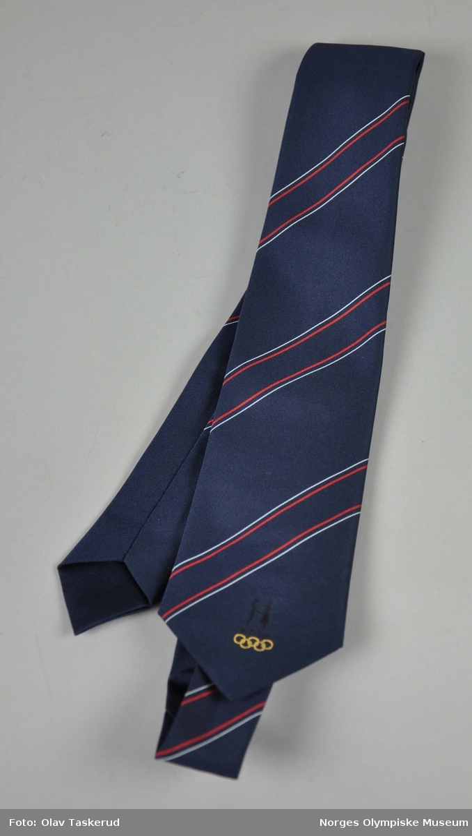 Blått slips  med NOK/NIFsin  logo innvevd i sort,  de olympiske ringene innvevd  i lys  sennepsgult,plassert til høyre nederst på slipset.Diagonale striper i hvitt og rødt.To like .