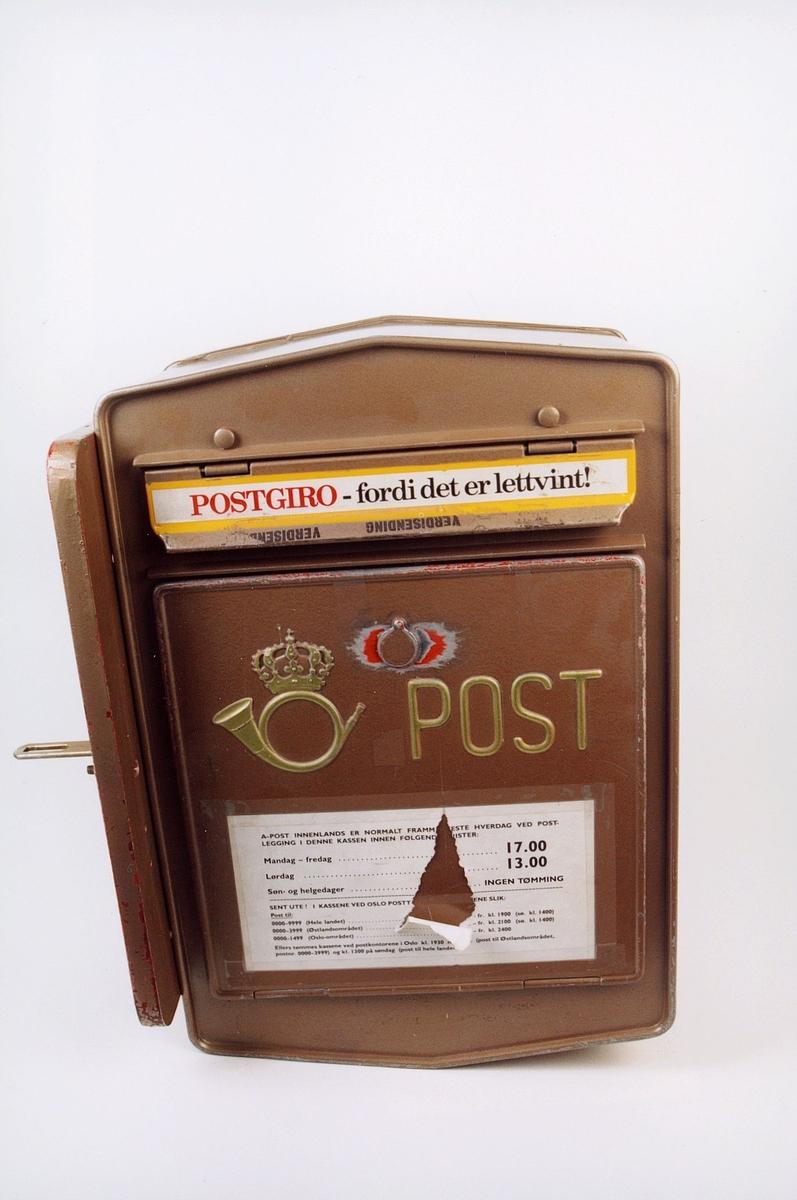 Manuell tømmepostkasse med opplysnigskilt for tømmetider. Låsbar.Posthorn og ordet POST. Reklame for Postgiro på innkastlokket. Veggfeste for sidemontering.