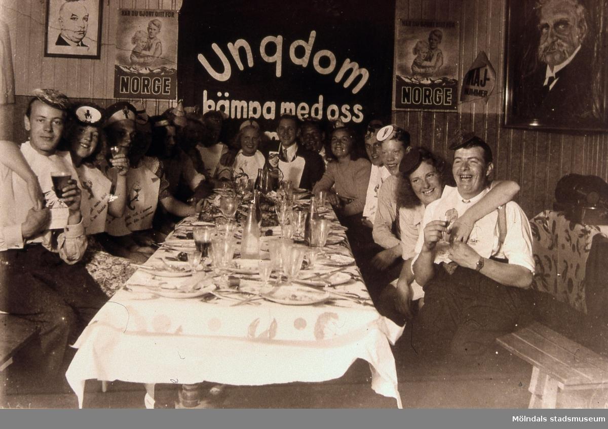 En samling kvinnor och män ur SSU har kräftskiva i klubblokalen (Konsums hus) i Toltorpsdalen, Mölndal, på 1940-talet. Reprofotografi. T 3:27.