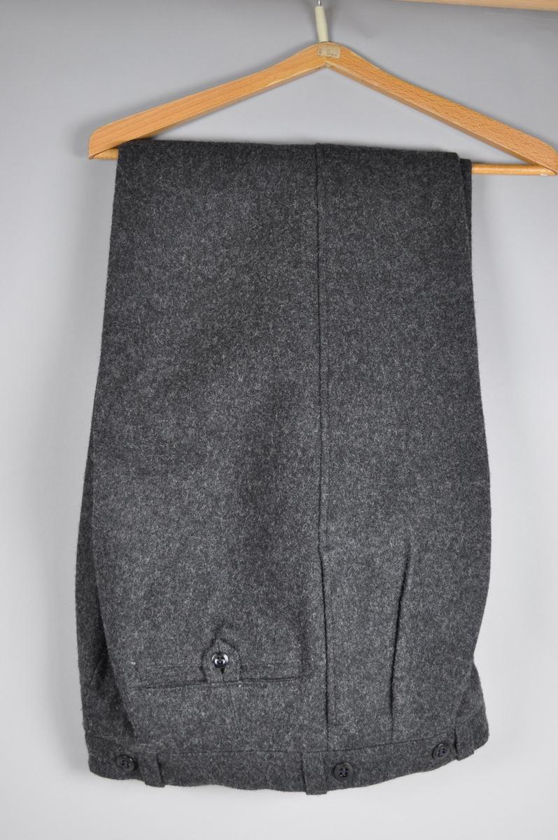 Grå uniformsjakke, dobbeltspent med påsatt sølvfargede knapper med posthorn. Jakken er i ullstoff med silke som innerstoff.  Det er tilhørende bukse.
