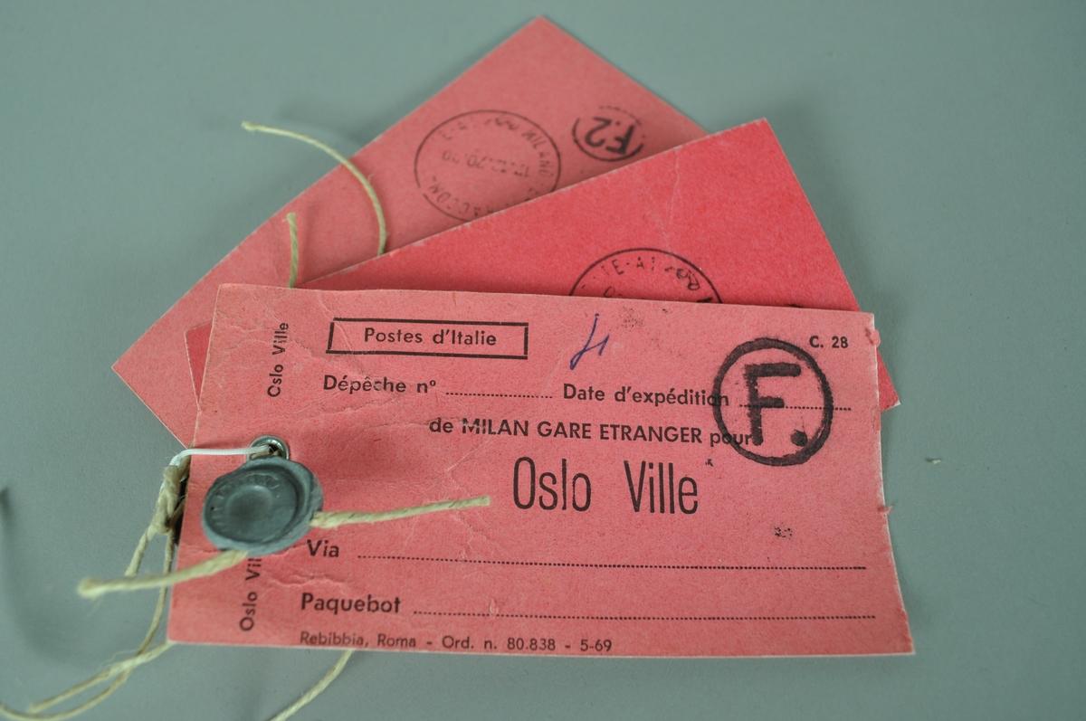Merkelapp, 2 stk i rødfarge. Merkelappene har hyssingrest og blyplombe med avtrykk fra utgangspostkontoret.