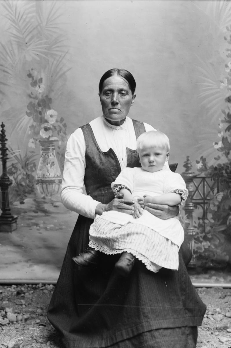 Portrett, kvinne med folkedrakt og lite barn på fanget, helfigur.