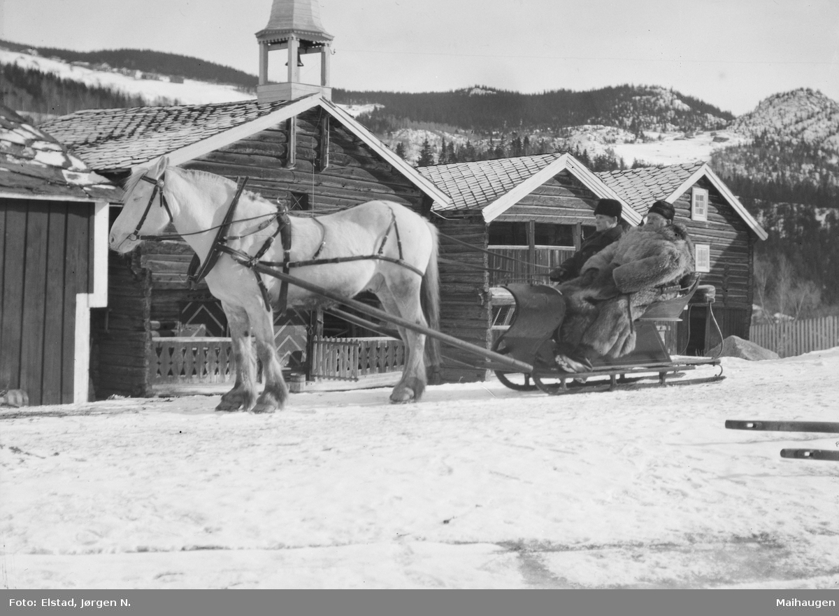 Ringebu. O. Chr. Elstad og Nils Bø, begge i kjørepels. Fjording foran spiss-slede. Gårdstun, stabbursklokke.