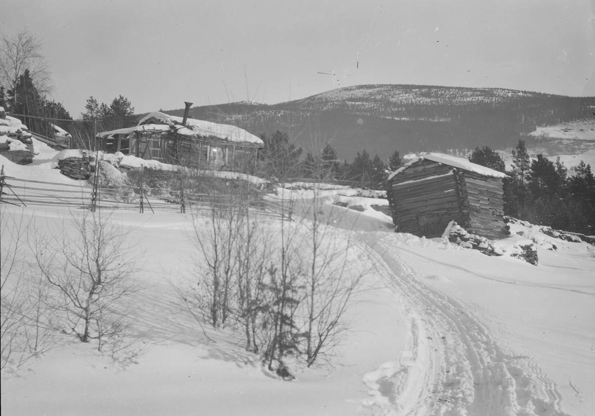 Ringebu kommune, Vinterbilde med to mindre tømmerbygninger. Snaufjell bak.