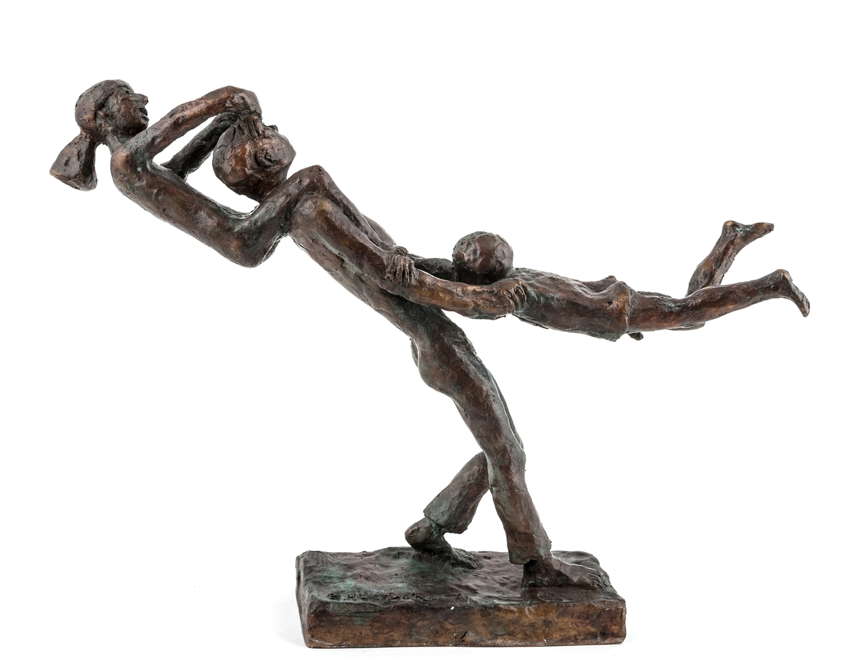 """En bronsskulptur som gestaltar hur en far leker """"karusell"""" med två barn, av konstnär Erik Höglund."""