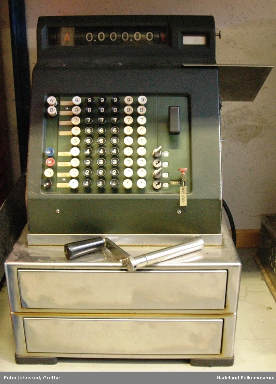 Mørk grønn med tastatur, håndsveiv og to pengeskuffer.
