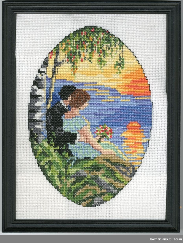 En ung man klädd i svart kostym sitter med armen runt en brunhårig kvinna med blå kortärmad klänning. Hon bär en bukett blommor i handen. De sitter på en sten framför en sjö och tittar ut på en solnedgång eller soluppgång. Bakom dem växer en björk.