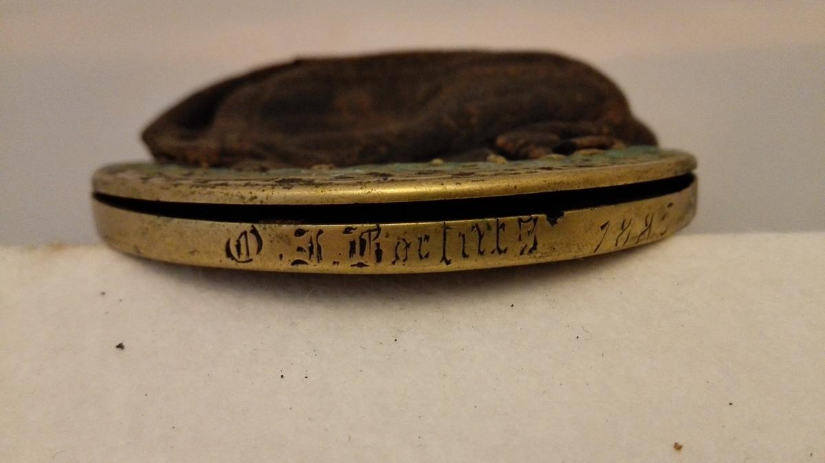 Liten kuleforma pung av skinn. Pungen vert låst med nøkkel, men nøkkelen manglar. Låsedel av messing, med rankeornament. På toppen av låsen er ingravert eit namn som er vanskeleg å tolka, og årstalet 1885.   Sjå foto.