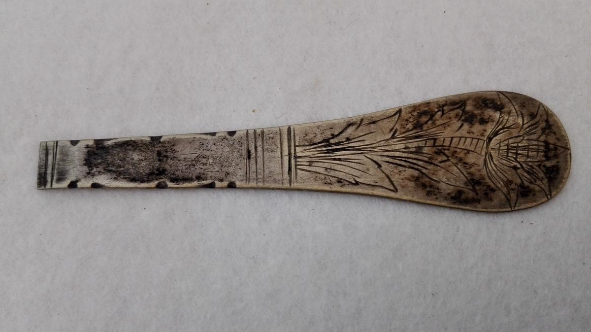 1 skaft av sölvske.  Skaft av en sölvske fra 1700 tallet fundet i jorden i kjökkenhaven paa Amble. Skaftet flatt, har paa forsiden indgravert en tulipan og paa baksiden med prikker bokstaverne F(?)GS (sjå original).  Gave fra G.F. Heiberg, Amble.