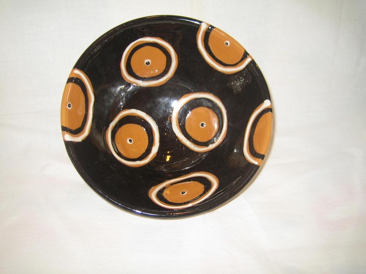 Rund skål i naturfärgad keramik på utsidan och svart glasyr på insidan, dekorerad med cirklar i vitt och svart med en vitsvart prick i mitten.