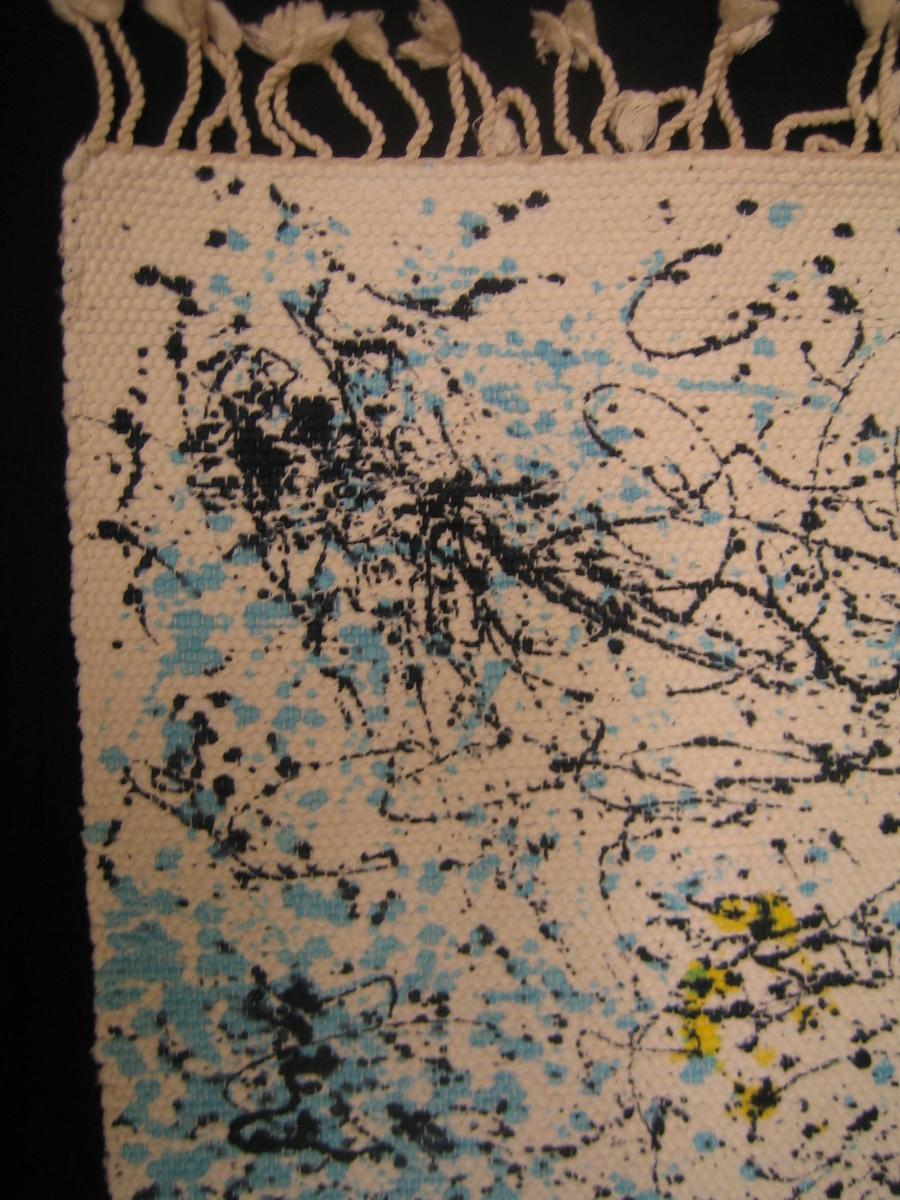 Matta vävd med halvblekt mattvarp i varpen och vita trasor som inslag. Mattan är dekorerad med stänk i svart, turkos och gult över hela mattan. Mattan är avslutad med en drejad frans.